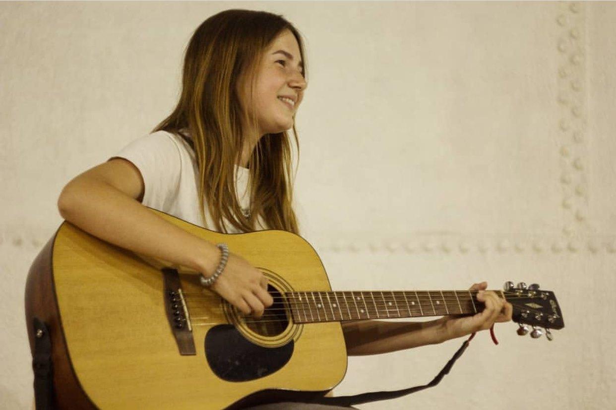 фотография девушки, играющей на гитаре